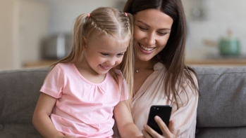 Close up of smiling young mother and small preschooler daughter relax at home together watch funny cartoon on smartphone