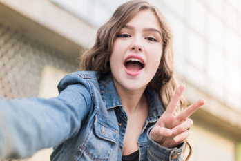 Close up portrait of a happy young woman showing peace sign in selfie